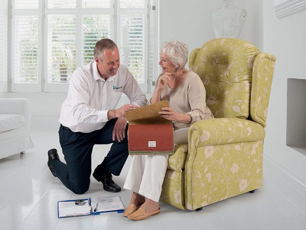 salesman with lady sitting in yellow upholstered chair