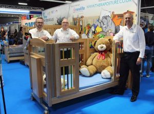 Salesmen stood around a cot with teddy bear