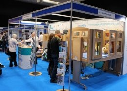 Man standing at cot bed exhibition stand