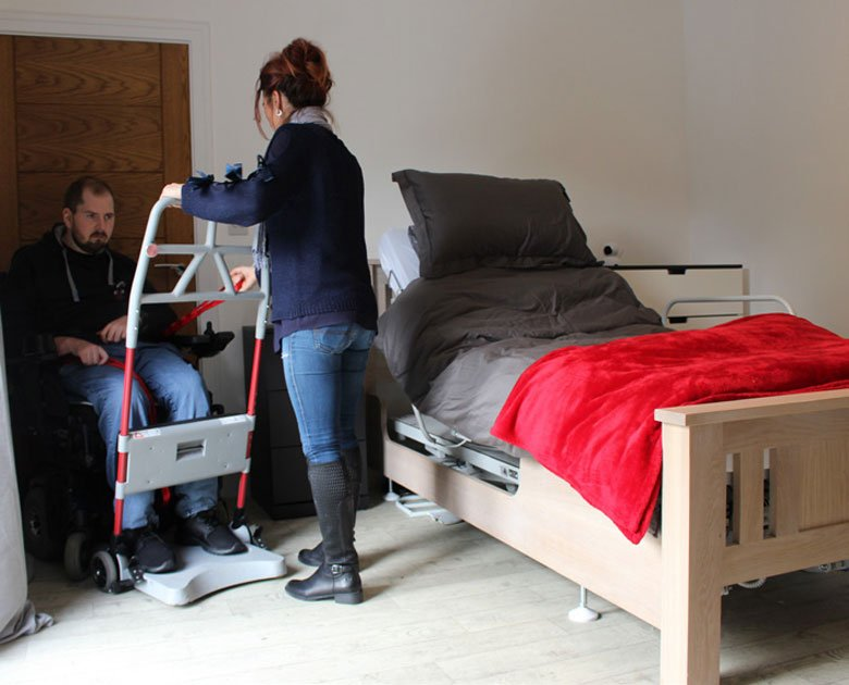 woman helping man into bed with lifter