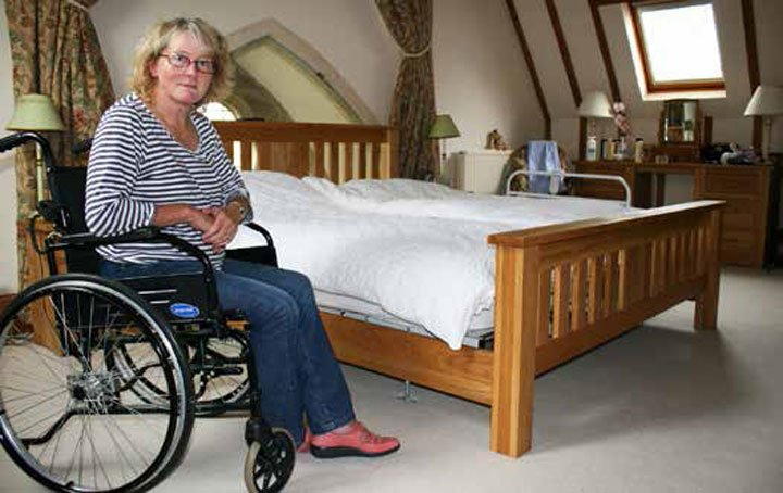 Woman in wheelchair next to bed