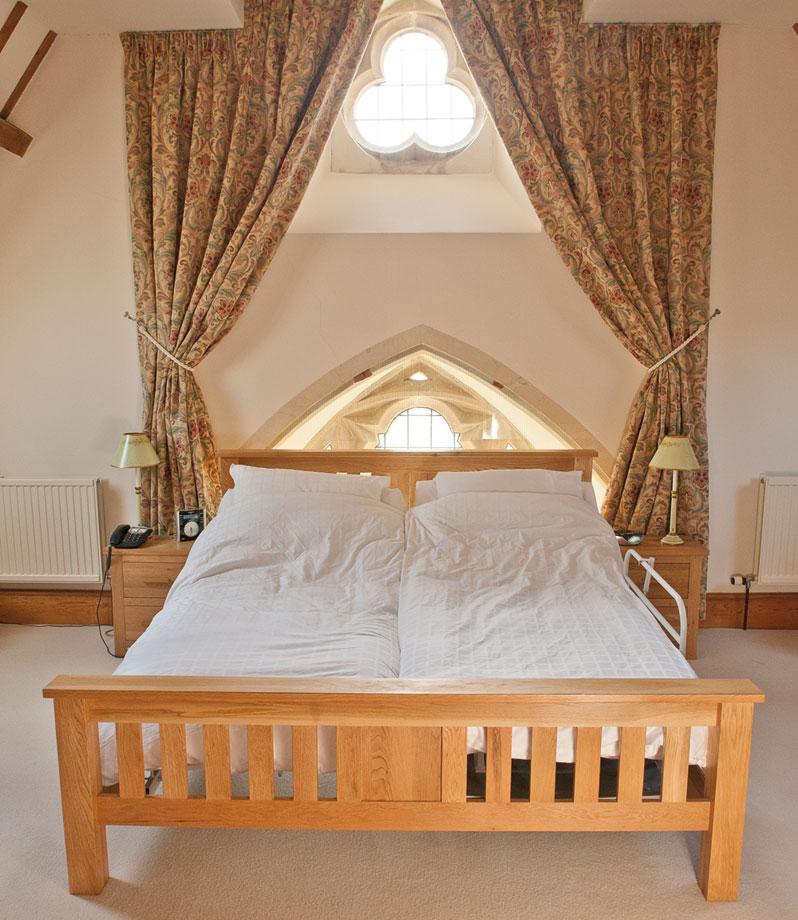 Double wooden Rotoflex bed under window